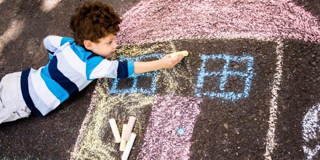 kid drawing chalk house on floor