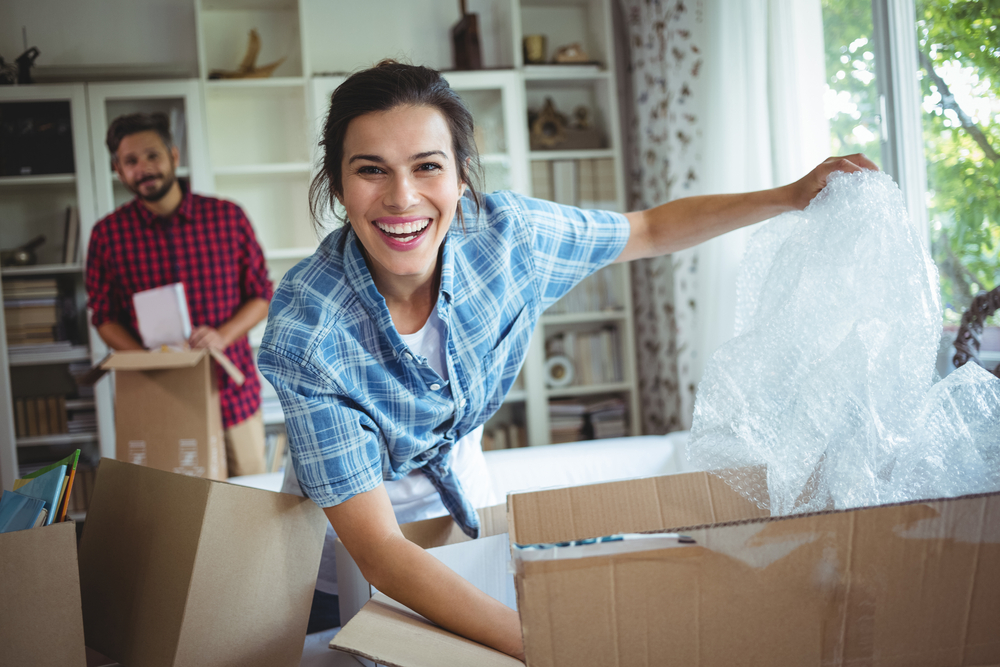 Woman happily unpacking boxes in her new home